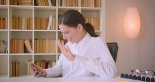 使用片剂的年轻可爱的白种人女实业家特写镜头画象笑愉快坐在书桌在办公室 股票视频