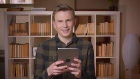 使用片剂的年轻可爱的白种人男生特写镜头射击在大学图书馆 影视素材