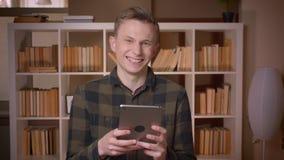 使用片剂的年轻可爱的白种人男生特写镜头射击看照相机在大学图书馆 影视素材