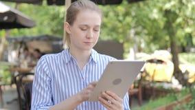 使用片剂的年轻女人,坐在咖啡馆大阳台 股票视频