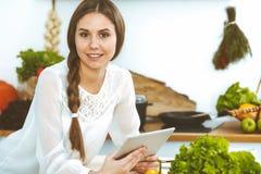 使用片剂的年轻女人,当烹调或做网络购物在厨房时 看照相机的女孩 ?? 免版税库存照片