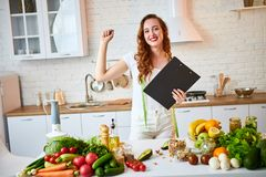 使用片剂的年轻美女,当烹调在现代厨房时 健康吃,维生素,节食,技术和人们 图库摄影