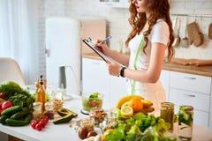 使用片剂的年轻美女,当烹调在现代厨房时 健康吃,维生素,节食,技术和人们 库存照片