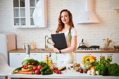 使用片剂的年轻美女,当烹调在现代厨房时 健康吃,维生素,节食,技术和人们 库存图片