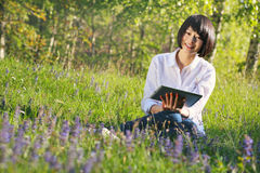 使用片剂的微笑的亚裔女孩室外 库存图片