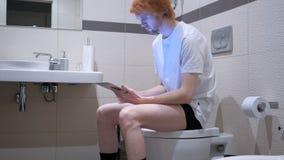 使用片剂的微笑的人在卫生间,洗脸台 免版税库存照片