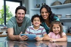 使用片剂的微笑的家庭在厨房里 免版税库存图片