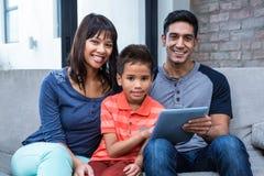 使用片剂的微笑的家庭在沙发 免版税库存图片