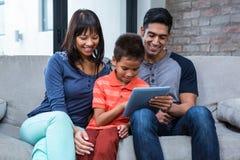 使用片剂的微笑的家庭在沙发 库存图片