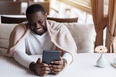 使用片剂的微笑的非裔美国人的人在咖啡馆 免版税库存图片