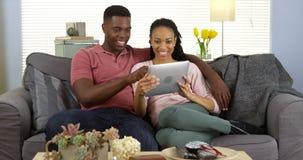 使用片剂的微笑的年轻黑夫妇在长沙发 免版税库存图片