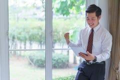 使用片剂的愉快的亚洲年轻英俊的商人 免版税库存照片