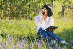 使用片剂的愉快的亚裔女孩室外 库存图片