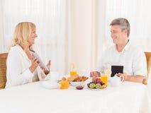 使用片剂的愉快的成熟健康夫妇和在早餐的ebook ereaders 图库摄影
