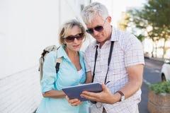 使用片剂的愉快的旅游夫妇在城市 免版税图库摄影
