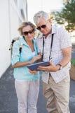 使用片剂的愉快的旅游夫妇在城市 库存照片