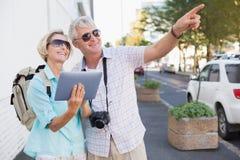 使用片剂的愉快的旅游夫妇在城市 免版税库存照片
