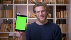 使用片剂的成人可爱的男生特写镜头射击和显示绿色屏幕对照相机在大学 股票录像