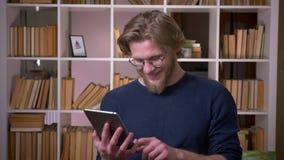 使用片剂的成人可爱的男生特写镜头射击愉快地微笑在大学图书馆户内 股票录像