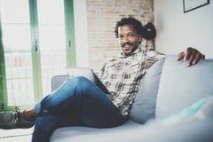 使用片剂的有胡子的微笑的美国非洲人为录影交谈,当放松在沙发在现代家时 概念 免版税库存照片