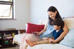 使用片剂的母亲和儿子 免版税库存图片