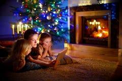 使用片剂的母亲和女儿由在圣诞节的一个壁炉 免版税库存图片