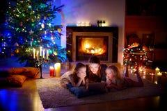 使用片剂的母亲和女儿由在圣诞节的一个壁炉 库存图片