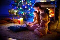使用片剂的母亲和女儿由在圣诞节的一个壁炉 免版税图库摄影