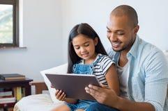 使用片剂的父亲和女儿 库存照片