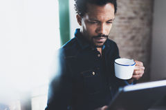 使用片剂的特写镜头观点的年轻有胡子的非洲人,当拿着白色陶瓷杯子手中在现代coworking时 库存照片