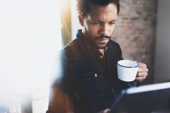 使用片剂的特写镜头观点的年轻有胡子的非洲人,当拿着白色陶瓷杯子手中在现代coworking时 库存图片