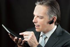 使用片剂的生意人佩带的耳机 免版税库存图片
