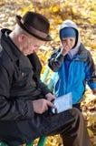 使用片剂的祖父观看由他的孙子 免版税库存照片