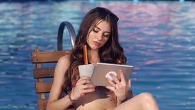 使用片剂的美丽的女孩和晒黑在水池附近 她喝鸡尾酒 股票录像