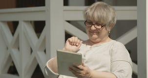使用片剂的资深妇女画象有玻璃的有乐趣户外在好日子在红色照相机的老人院射击 影视素材