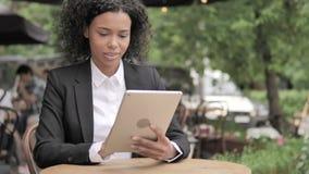 使用片剂的非洲妇女,坐在室外咖啡馆 股票视频
