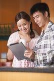 使用片剂的年轻夫妇在厨房里 免版税库存图片