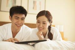 使用片剂的年轻夫妇在床上 库存图片
