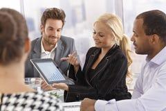 使用片剂的年轻女实业家在会议上 免版税库存图片