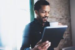 使用片剂的年轻有胡子的非洲人特写镜头,当拿着白色杯子咖啡手中在现代coworking的办公室时 库存图片
