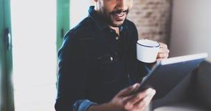使用片剂的年轻有胡子的非洲人特写镜头,当拿着白色杯子手中在现代coworking的办公室时 概念 免版税库存照片