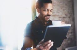 使用片剂的年轻有胡子的非洲人特写镜头,当拿着白色陶瓷杯子手中在现代coworking的办公室时 免版税图库摄影