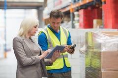 使用片剂的经理,当工作者扫描包裹时 免版税库存图片