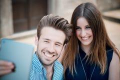 使用片剂的年轻美丽的夫妇恋人 免版税库存图片