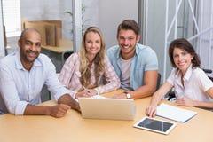 使用片剂计算机和膝上型计算机的微笑的商人 免版税库存照片