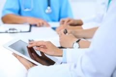 使用片剂计算机在医疗会议上,特写镜头的医生 小组背景的同事 免版税库存照片