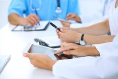 使用片剂计算机在医疗会议上,特写镜头的医生 小组背景的同事 库存照片