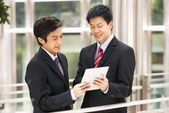 使用片剂计算机的二个中国生意人 免版税库存照片