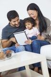 使用片剂计算机的亚裔夫妇家庭孩子 免版税库存图片