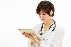 使用片剂计算机的亚裔女性医生 免版税库存图片